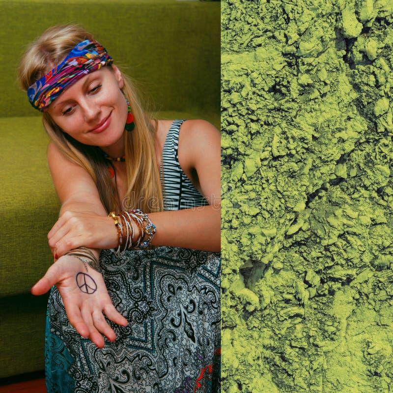 Hippie-Mädchen, das auf dem Grünhintergrund sitzt lizenzfreies stockfoto