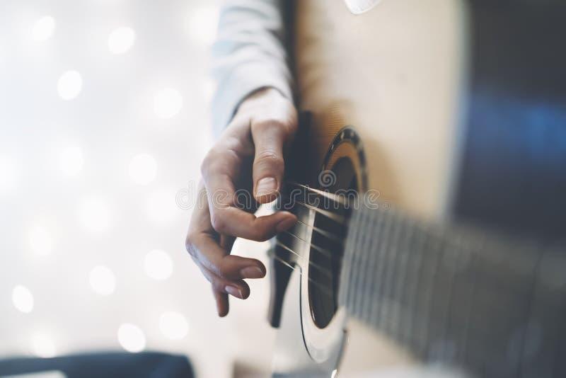 Hippie-Mädchen, das Gitarre in einer Haupt- Atmosphäre, Person studiert auf Musikinstrument auf Glühen bokeh Weihnachten-illimina lizenzfreie stockfotos