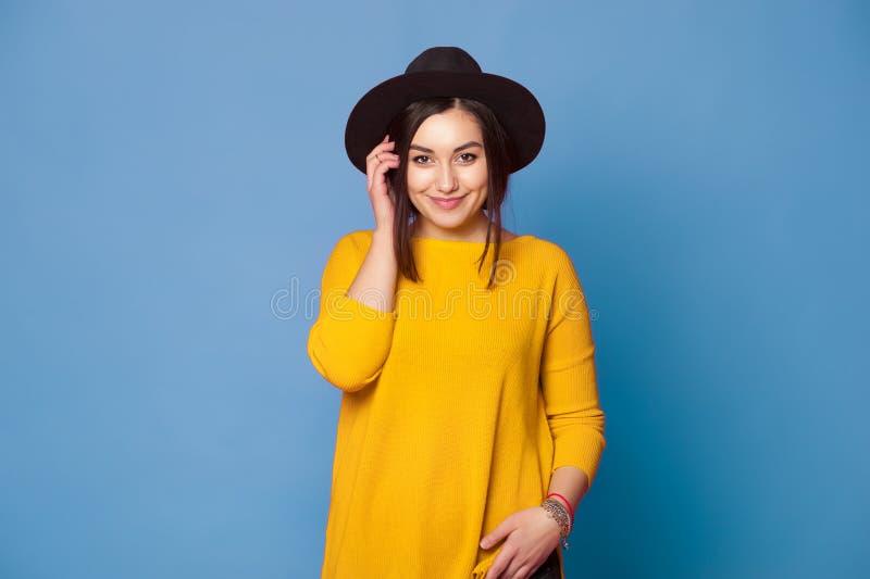Hippie-Mädchen, das stilvollen Hut und gelbe Strickjacke auf Blau trägt lizenzfreie stockfotos