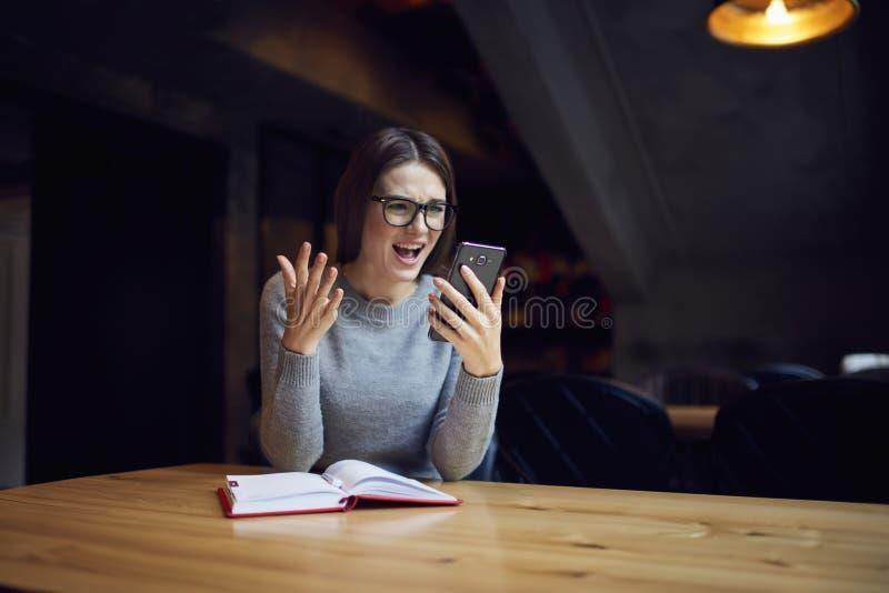 Hippie-Mädchen in den Brillen Schocknachrichten am Handy lesend stockbild
