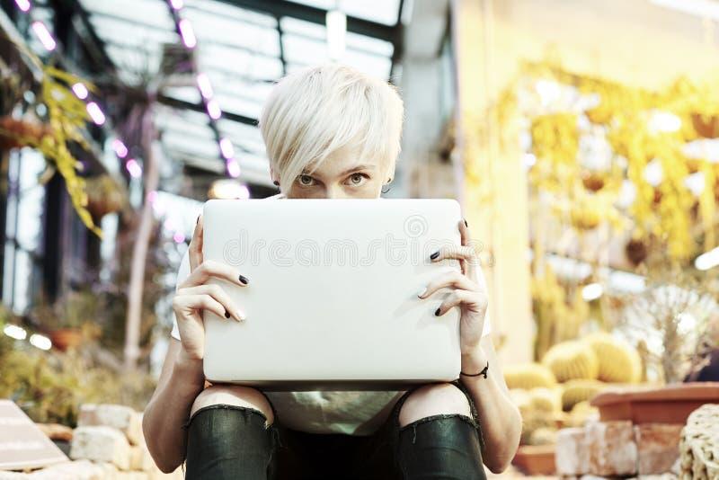 Hippie-Mädchen mit dem blonden Haar versteckt hinter der geöffneten Laptop-Computer, sitzend auf Treppe in einem Park im Freien,  lizenzfreie stockfotos