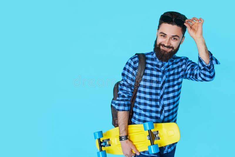 Hippie-Mann über dem bunten blauen Hintergrund, der gelbes Skateboard hält lizenzfreies stockfoto