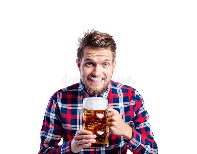Hippie-Mann in überprüftem trinkendem Bier des Hemdes, Atelieraufnahme stockfotografie