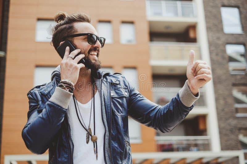 Hippie-Mann, der Daumen bei der Unterhaltung am Telefon hochhält stockbild