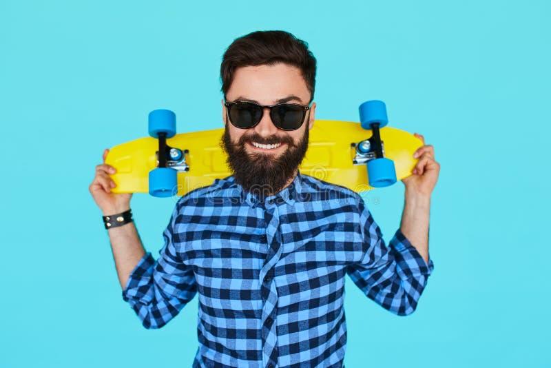 Hippie-Mann, der ein helles vibrierendes gelbes Skateboard hält lizenzfreies stockbild