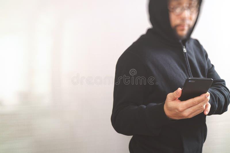 Hippie-Mann in einer Haubenhand unter Verwendung Handyzahlungen on-line-s stockfoto