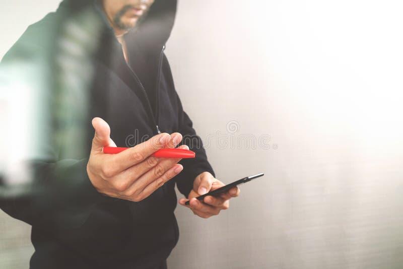 Hippie-Mann in einer Haubenhand unter Verwendung Handyzahlungen on-line-s stockbilder