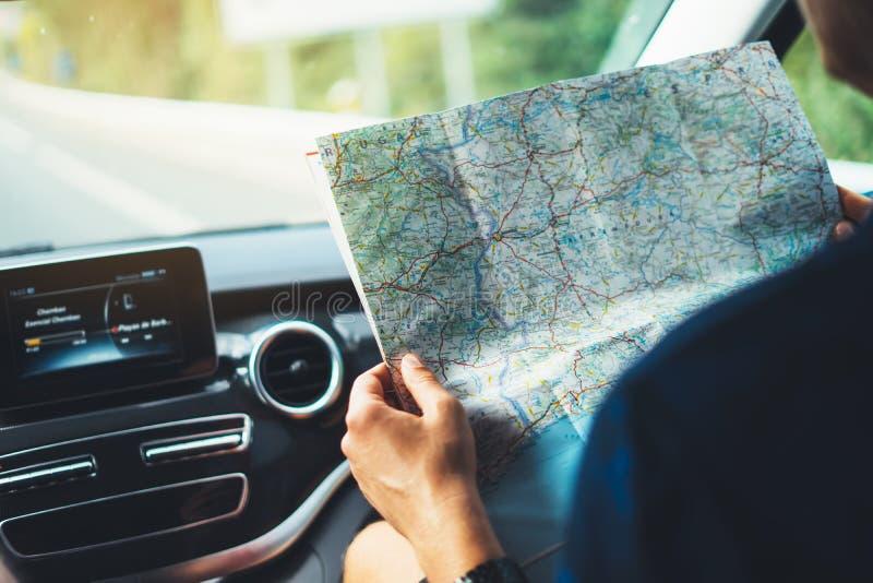 Hippie-Mannschauen und -punktfinger auf Standortnavigationskarte im Auto, im touristischen Reisendfahren und im Griff im Mann übe lizenzfreies stockbild