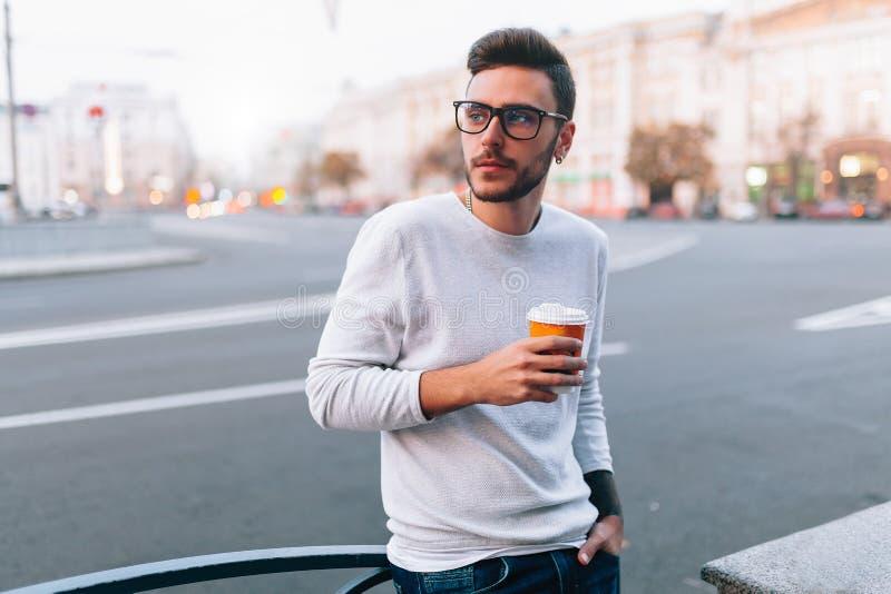 Hippie-Mannstellung mit dem Mitnehmerkaffee, plesantly lächelnd und gehen auf Thstadtstraße Glücklicher sorgloser hübscher Kerl i stockbild