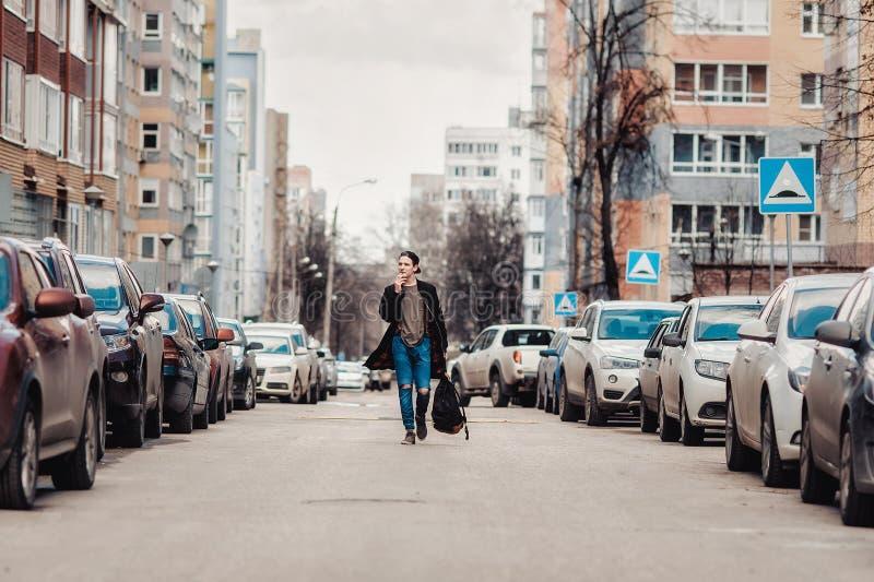 Hippie marchant autour de la ville sur la rue parmi des voitures photos libres de droits