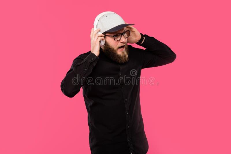hippie masculin barbu déçu enlevant des écouteurs d'isolement photo stock