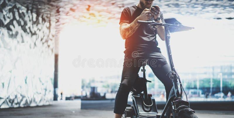 Hippie masculin tatoué barbu à l'aide du téléphone portable après la monte en le scooter électrique dans la ville wide photo libre de droits