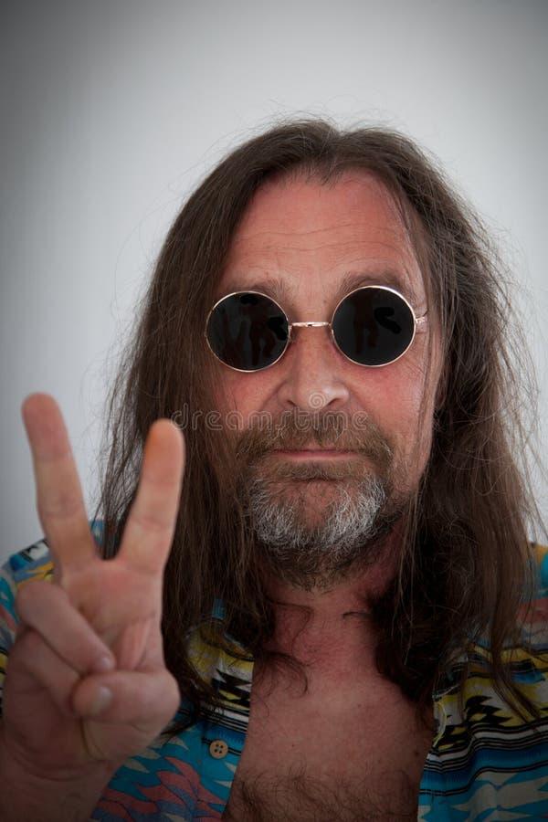 Hippie masculino con el pelo largo del largo de hombros que hace un signo de la paz con sus fingeres foto de archivo
