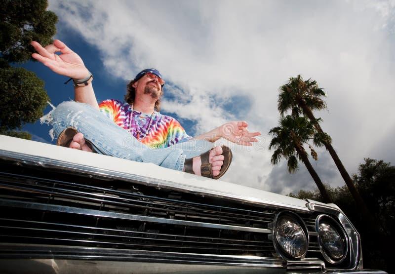 Hippie Meditating en el capo motor del coche fotografía de archivo