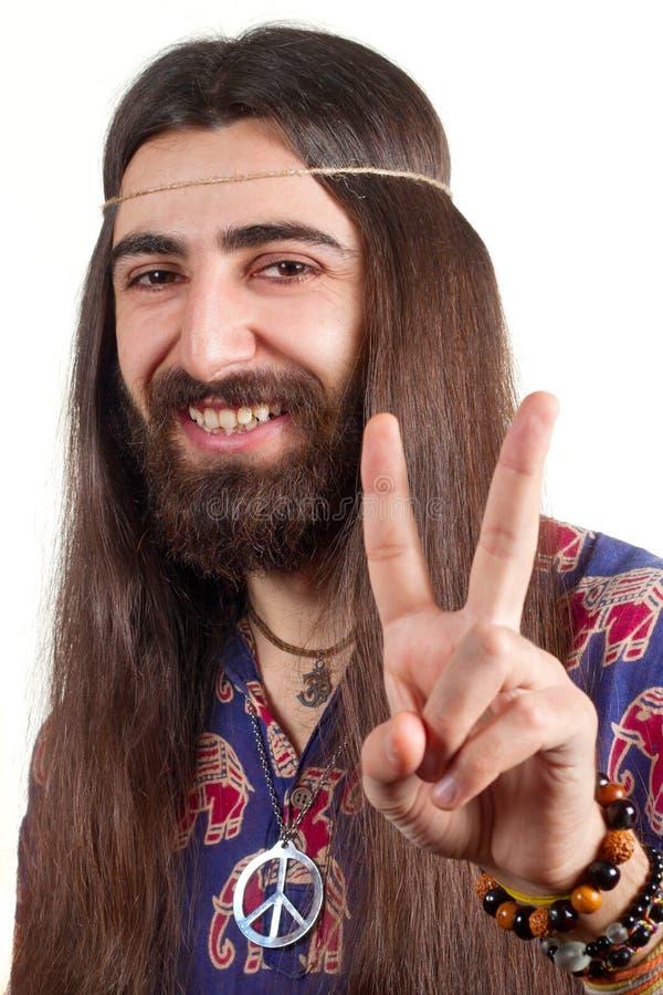 Hippie met lang haar dat vredesteken maakt stock foto's