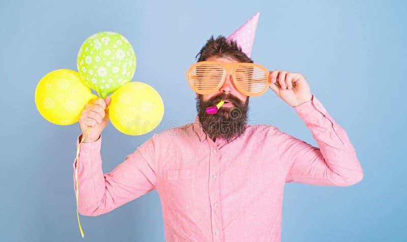 Hippie mit buschigem Bart Geburtstag feiernd Bärtiger Mann aufwerfend in der Geburtstagskappe mit enormen Gläsern und hell lizenzfreies stockfoto