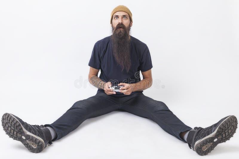 Hippie mit einem Gamecontroller auf dem Boden lizenzfreie stockbilder