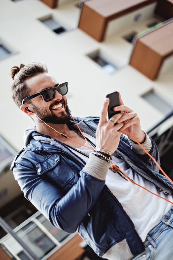 Hippie mit Kopfhörern lächelnd und Mitteilung lesend stockfoto