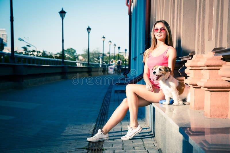 Hippie-Mode-Mädchen und ihr Hund in der Stadt lizenzfreie stockfotos
