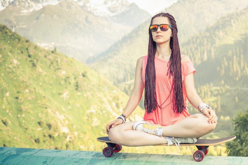 Hippie-Modemädchen, welches das Yoga, entspannend auf Skateboard am Berg tut lizenzfreie stockfotos