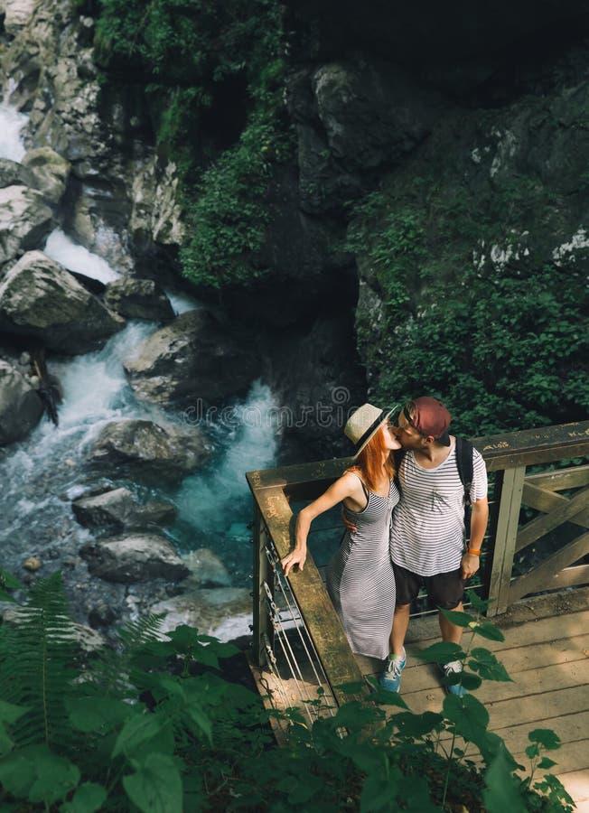 Hippie-Paare, die auf dem Hintergrund von einem Gebirgsfluss wandern stockfotografie