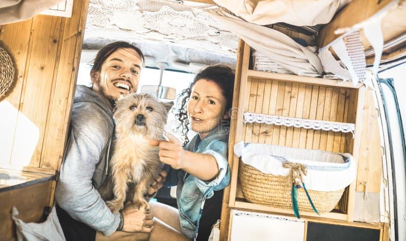 Hippie-Paare mit dem netten Hund, der zusammen auf Oldtimermehrzweckfahrzeug reist stockfotos