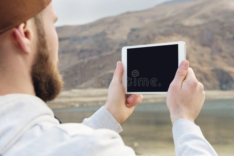 Hippie-Person, die in der Handdigitalen Tablette mit leerem leerem Bildschirm, Mannphotographie auf Computer auf Hintergrundnatur stockbild
