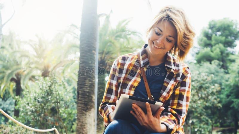 Hippie-Personenholding in der Handdigitalen Tablette mit Schirm, Lächelnlesung des jungen Mädchens auf Computer auf Hintergrundna lizenzfreie stockbilder