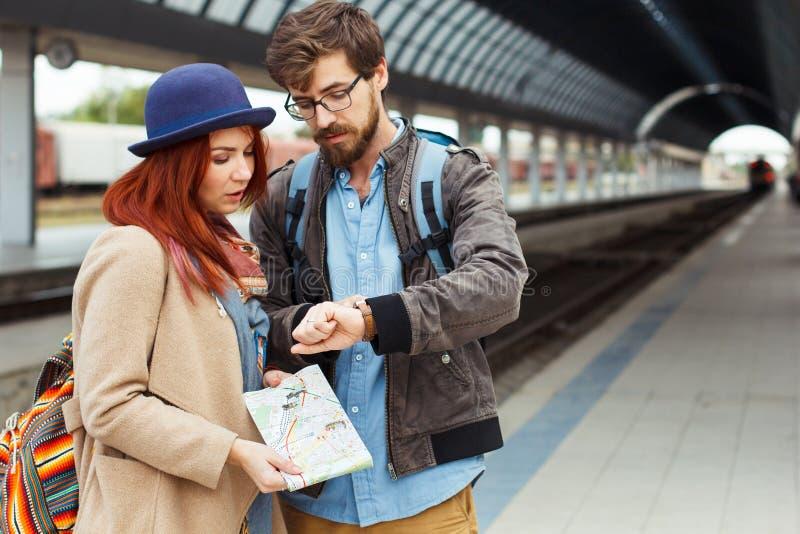 Hippie-Reisendpaare, die intelligente Uhr beim Warten auf den Zug am Bahnhof betrachten Autumn Time Frau lizenzfreie stockfotos