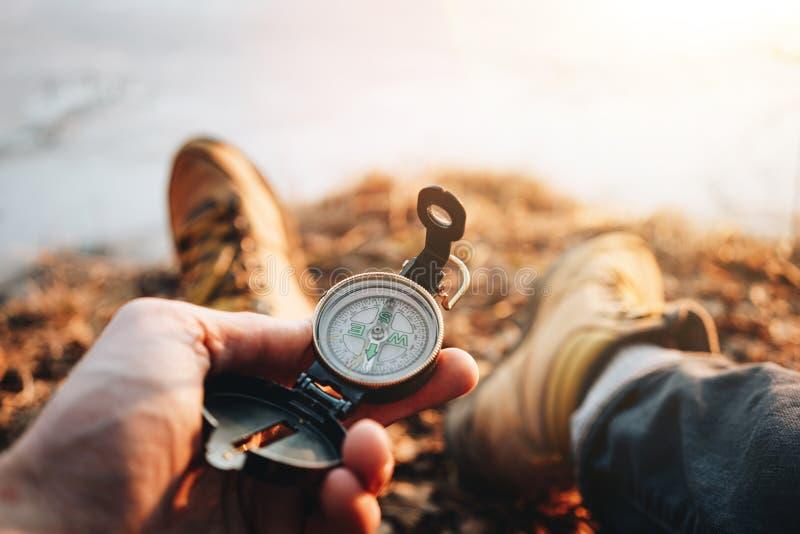 Hippie-Reisendsitzen und Kompass des Griffs in der Hand Pov-Ansicht Unscharfer Hintergrund lizenzfreie stockbilder
