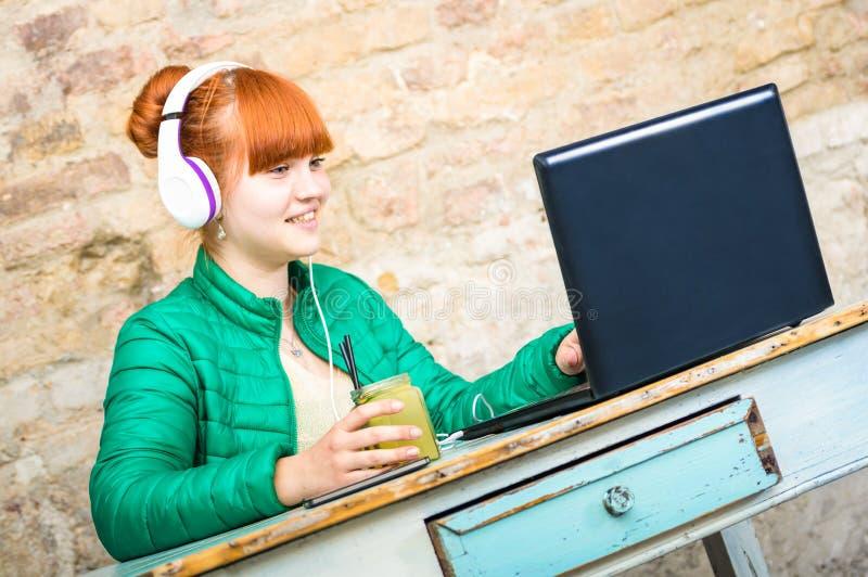 Hippie-Rothaarigefrau mit Kopfhörer unter Verwendung der Laptop-Computers stockbild