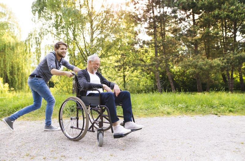 Hippie-Sohn, der mit behindertem Vater im Rollstuhl am Park läuft stockfoto