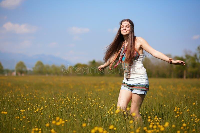 Hippie sonriente en campo de flores del verano fotografía de archivo libre de regalías