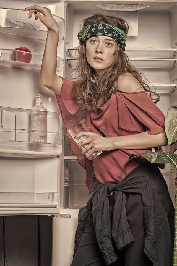 Hippie standing with glass of milk at open fridge door royalty free stock images