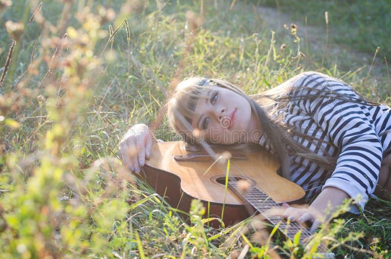 Hippie-stil flicka som poserar med en gitarr royaltyfri bild