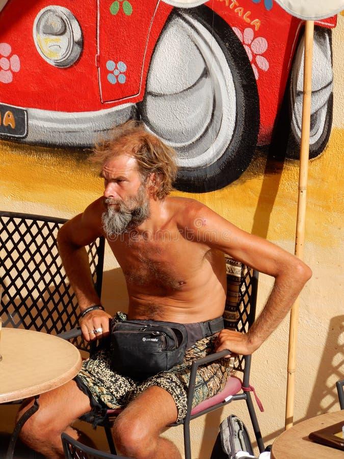 Hippie viejo que goza del sol después de fumar un cigarrillo fotos de archivo