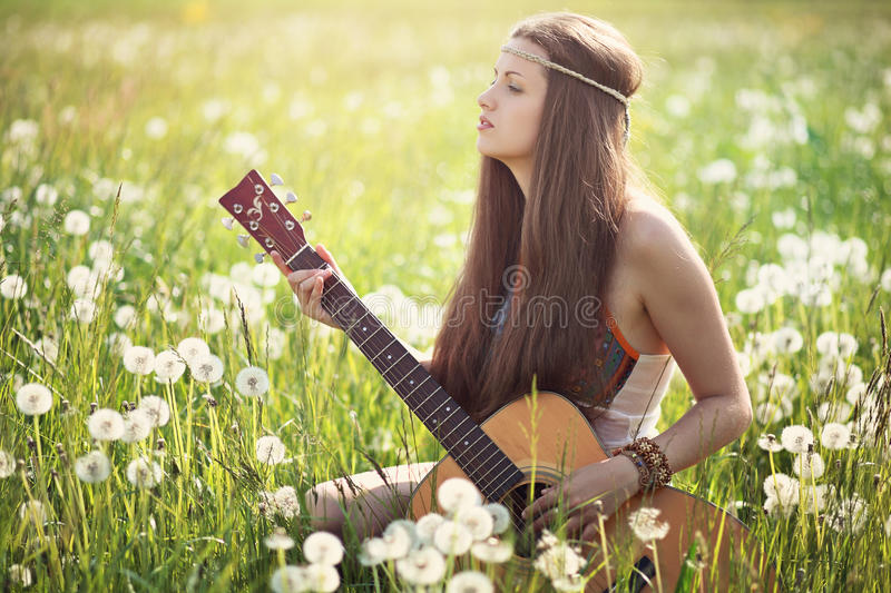 Hippie woman with guitar in summer meadow royalty free stock photos