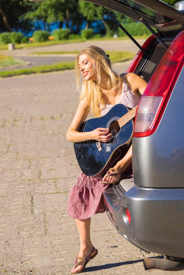 Hippie woman playing guitar in van car. Hippie looking woman with long skirt sitting in van vehicle camper trailer with guitar, playing peacefully music in stock photo