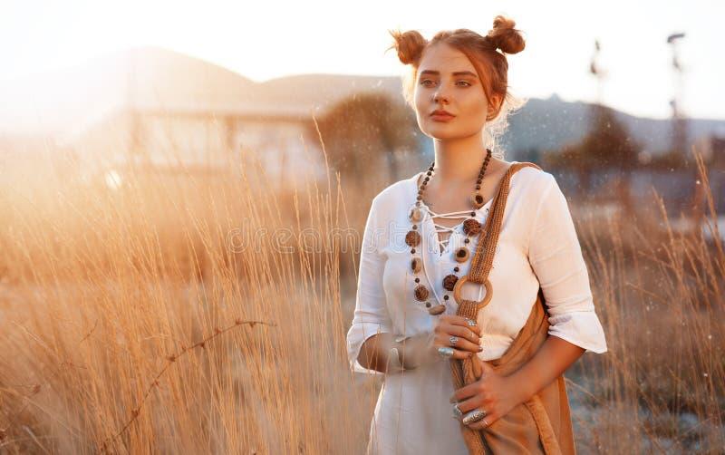 Hippieflickan i prydnadbohostil står i ett fält på solnedgången arkivfoto