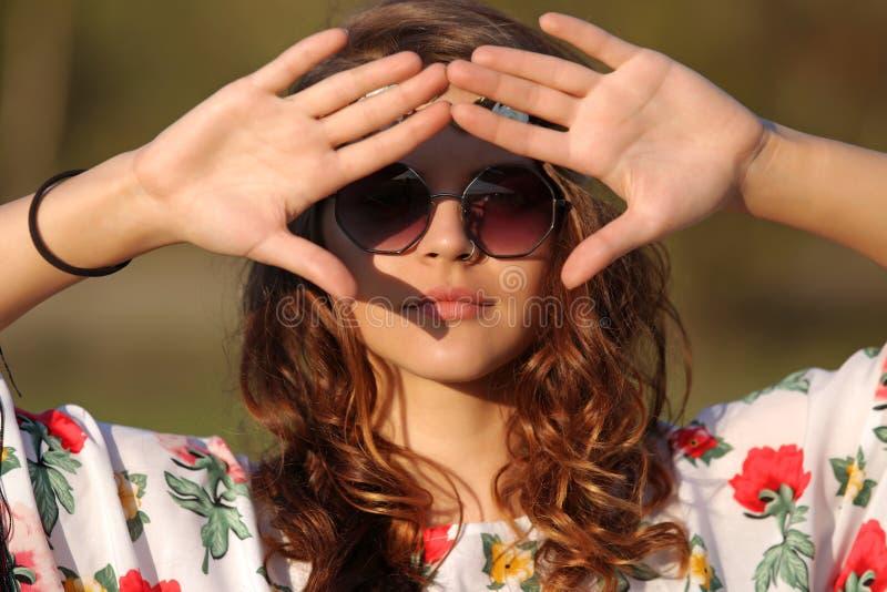 Hippieflickan i solglasögon täcker hennes framsida från solhanden utomhus arkivbilder