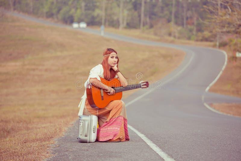 Hippiekvinna på en bygdväg royaltyfri bild