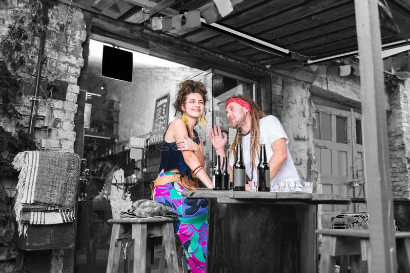 Hippiekvinna som bär ljus kjolkänsla som förbluffar sammanträde nära hennes pojkvän arkivbild