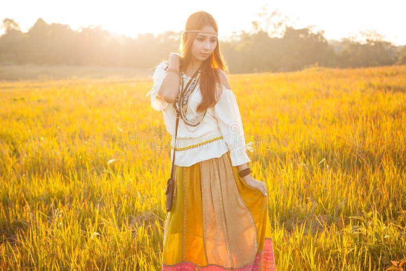 Hippiekvinna som poserar i guld- fält arkivbild