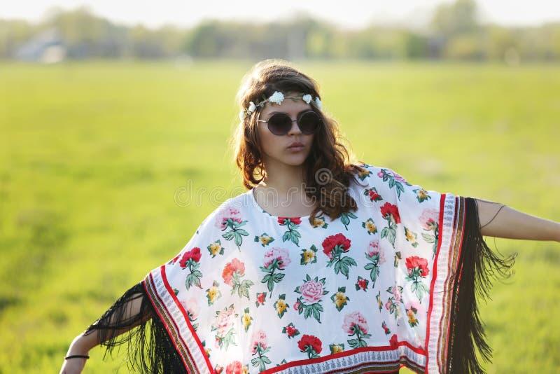 Hippien för ung kvinna i solglasögon som utomhus står, beväpnar utsträckt utomhus royaltyfria foton