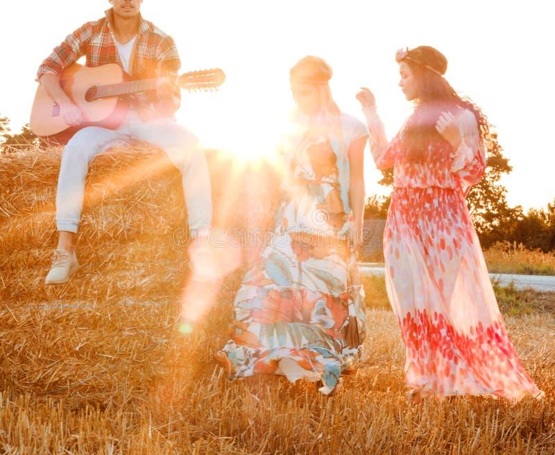 Hippievänner med gitarren i ett vetefält arkivfoton