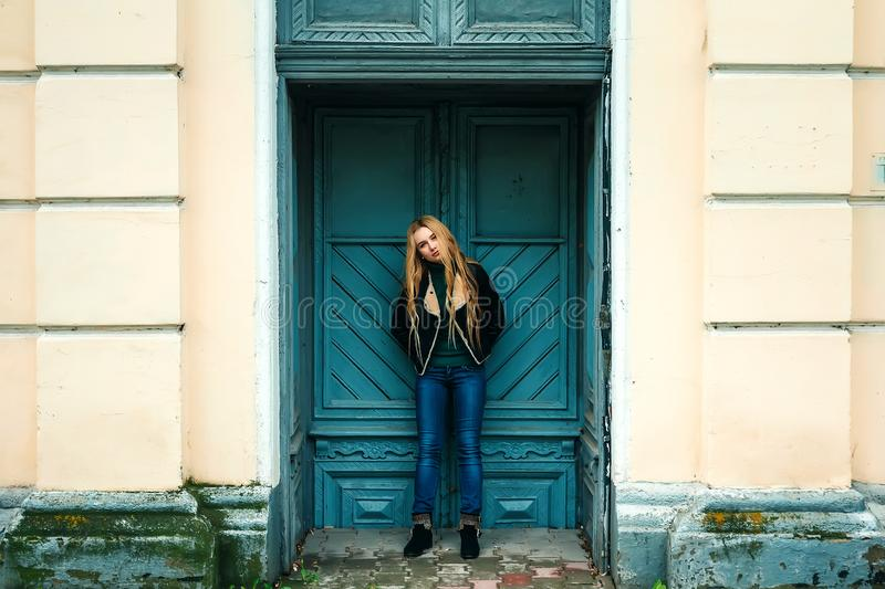 Hippy blond girl in hat holding a marijuana leaf in the mouth and wearing retro sunglasses, leaning on the old door.. Soft lights stock photo