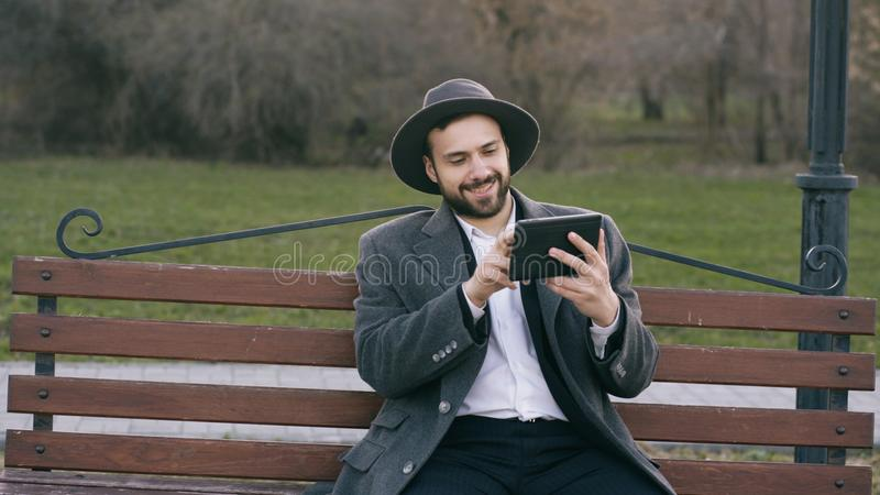 Hipser creative business man in hat using tablet pc computer and sitting on city street bench in park during break royalty free stock image