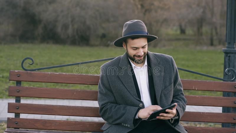 Hipser creative business man in hat using tablet pc computer and sitting on city street bench in park during break royalty free stock images