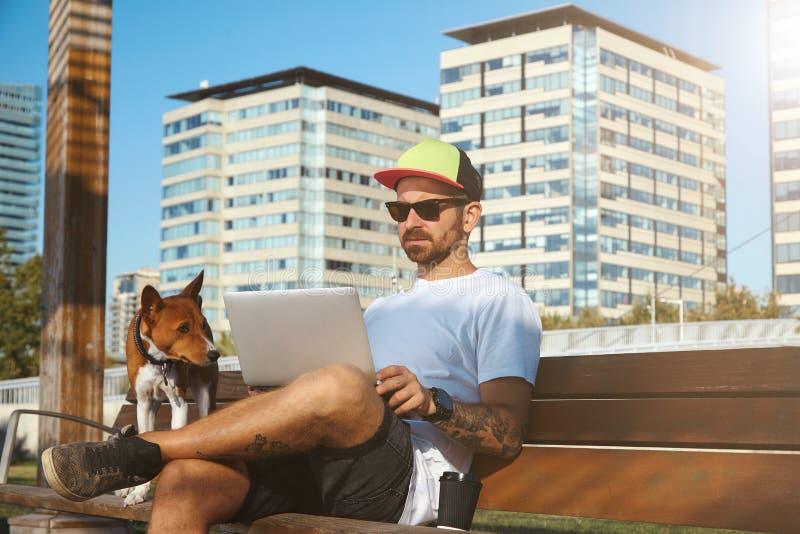 Hipster με το lap-top, τον καφέ και το σκυλί στοκ φωτογραφία με δικαίωμα ελεύθερης χρήσης