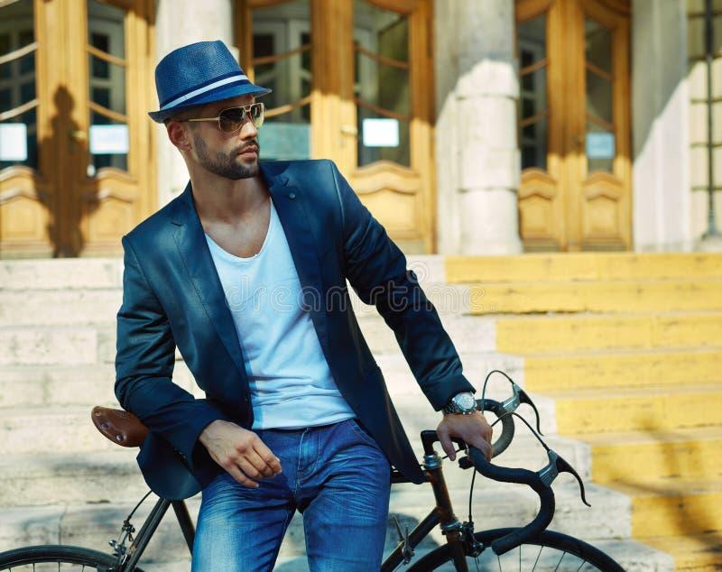 Hipster στο καπέλο και γυαλιά ηλίου με το ποδήλατο στην πόλη στοκ εικόνα με δικαίωμα ελεύθερης χρήσης